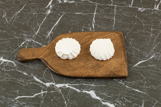 Two delicious marshmallow on wooden cutting board.