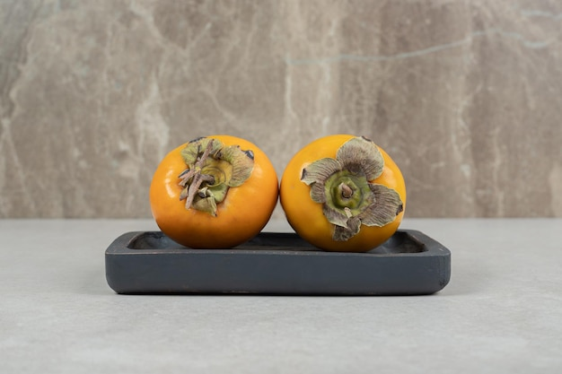 Two delicious persimmons on black plate