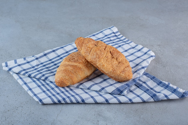 Two delicious sweet croissants with tablecloth on stone.