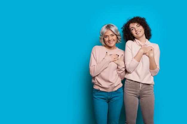 곱슬 머리를 가진 두 기쁨 백인 자매는 빈 공간이있는 파란색 벽에 포즈를 취하는 동안 심장 근처에 손을 잡고 있습니다.