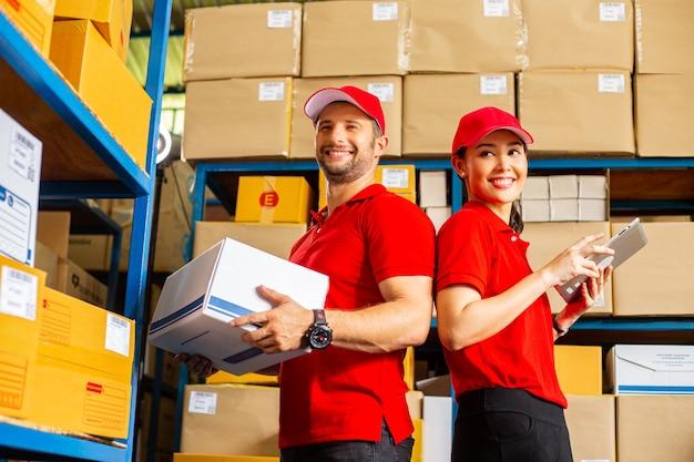 Два работника службы доставки проверяют и готовят коробку для отправки заказчику.