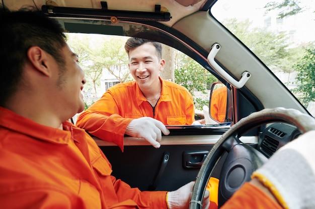 Два работника службы доставки разговаривают