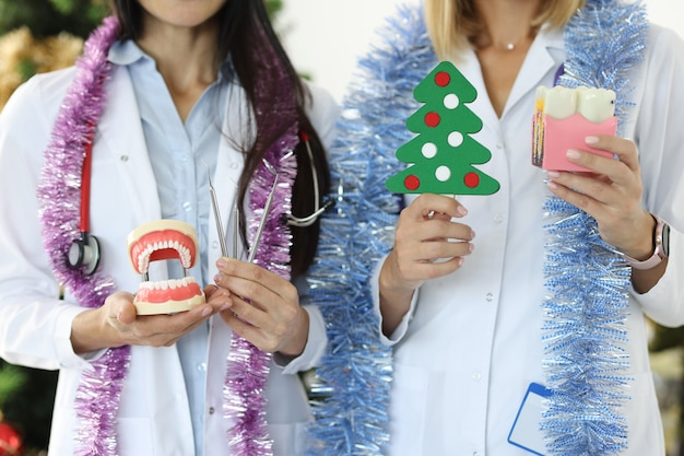 Two dentist doctors are holding a dental instrument on background of christmas tree celebrating