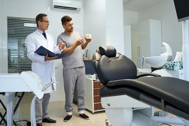 사무실에서 치아 복제품을 보고 있는 두 명의 치과의사