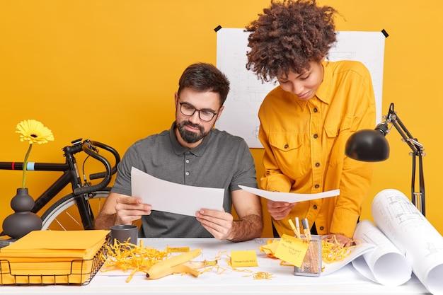 2人の設計作業員が、デスクトップでポーズをとる書類に集中して新しい建物の設計を準備し、適切な解決策を見つけようとします