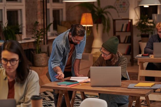 사무실에서 노트와 노트북으로 함께 작업하는 프로젝트를 논의하는 두 디자이너