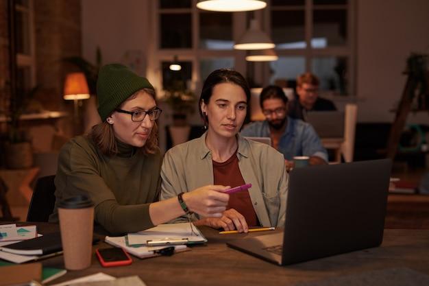 테이블에 앉아 사무실에서 팀에서 일하는 직장에서 노트북을 사용하는 두 명의 디자이너