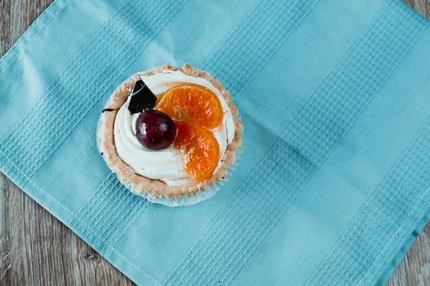 Two desserts, one chocolate with cherries, the other white cream with plums and tangerines