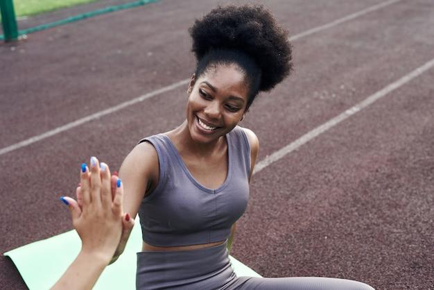 2人の異なるアフリカ人とイラン人のガールフレンドが運動中にお互いに5人を与えます。路上でのフィットネスクラスのために一緒に屋外で応援するスポーツの若い女性。閉じる。