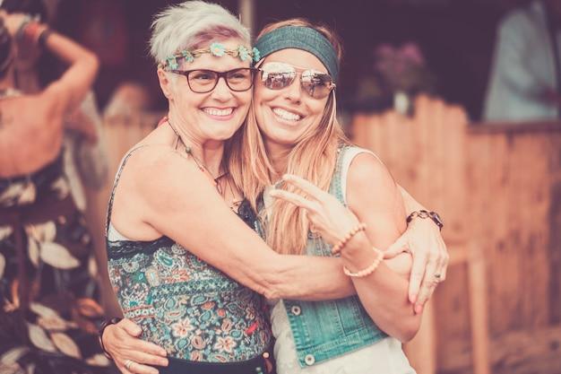 두 명의 다른 연령대 여성 친구가 포옹하고 미소와 재미와 함께 사랑에 머물러 있습니다-쾌활한 다른 연령대의 백인 사람들-어머니와 딸-빈티지 컬러 필터의 행복한 히피 사람들