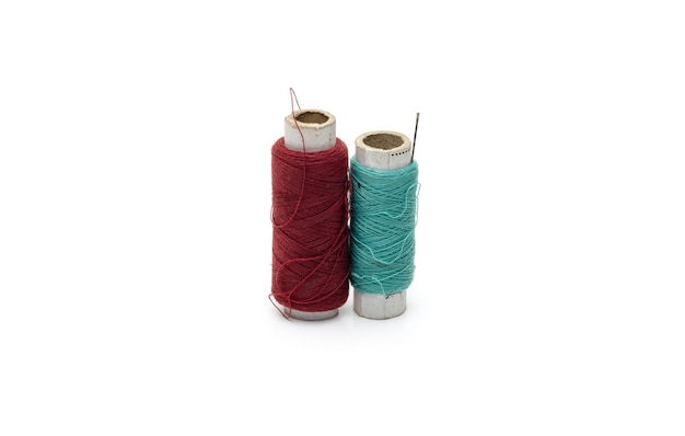 Two different color yarn threads spools on an isolated white background