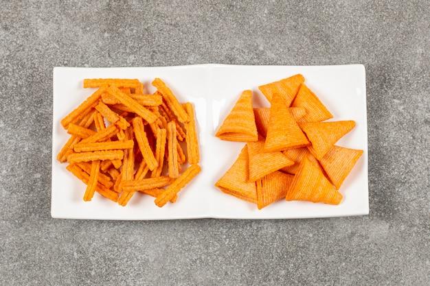 Due chip di forma diversa sul piatto bianco.
