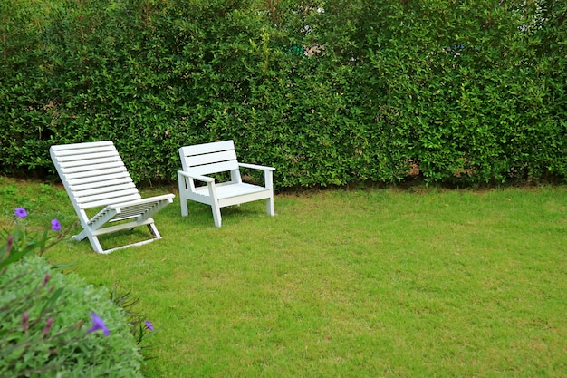 Two different type of white colored wooden chairs in vibrant green garden