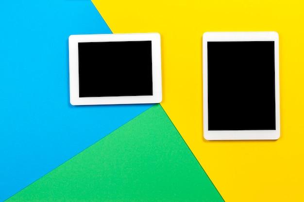 明るい青緑と黄色の背景に 2 つのデジタル タブレット