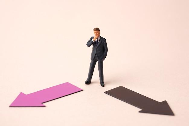 ミニチュアビジネス男と2つの方向矢印