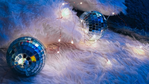 Two disco balls lying down on cozy blanket with christmas garland light. cozy home interior. home sweet home. after party. new year decoration.