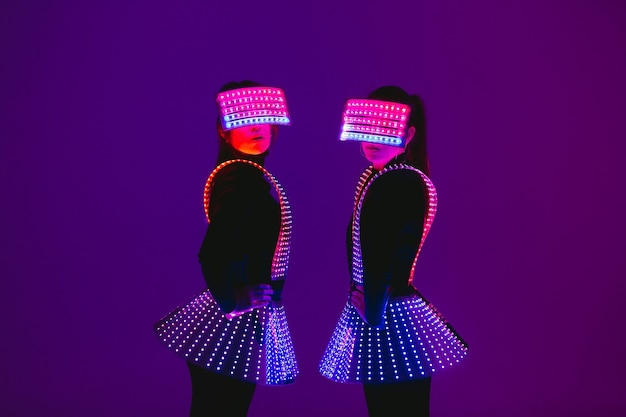 Two  disco dancers move in uv costumes.