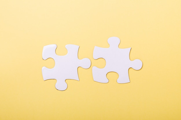 Two disconnected jigsaw puzzle pieces on yellow