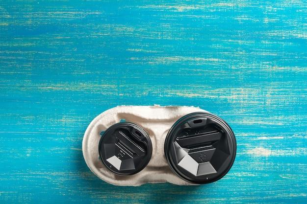 青い木製の表面に2つの使い捨て紙コップコーヒーと使い捨てカップホルダー