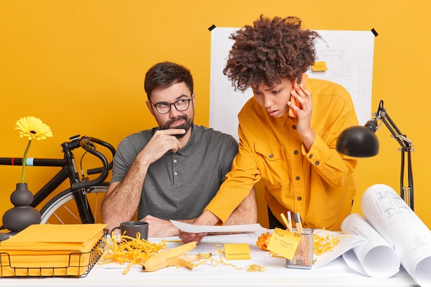 Two diverse architects talk about interior planning and organization of working process pose at coworking space. puzzled afro american woman discuss details of cooperation while calling partner