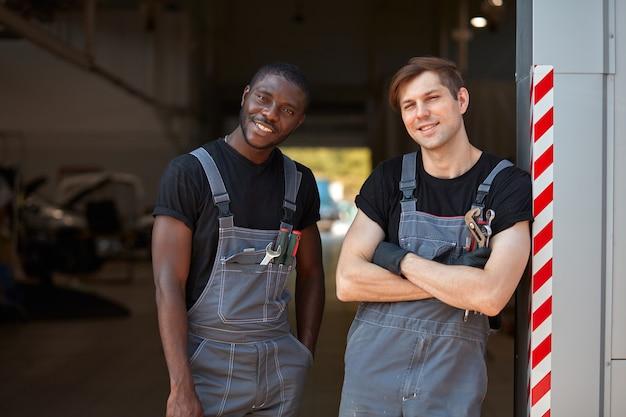 2人の多様な自動車整備士の男性が職場で休んでいます