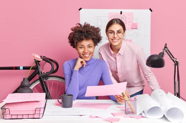 두 명의 다양한 창의적인 여성이 협력하여 청사진을 새로운 프로젝트에서 작업하는 코 워킹 스페이스에서 포즈를 취합니다.