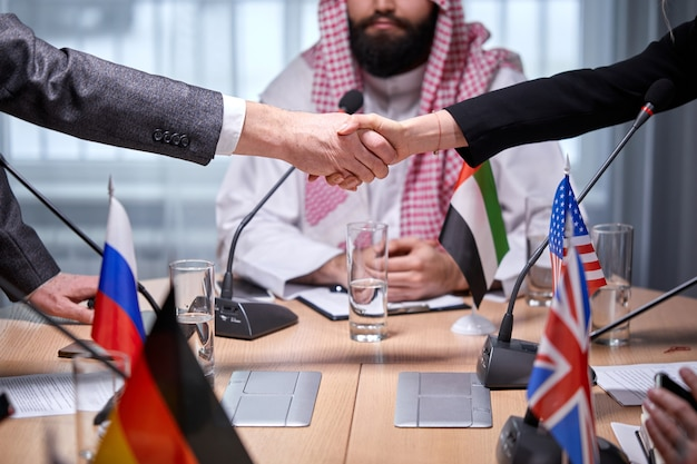 Two diverse delegates shaking hands after agreement in the presence of arabic sheikh during meeting in boardroom. international business concept
