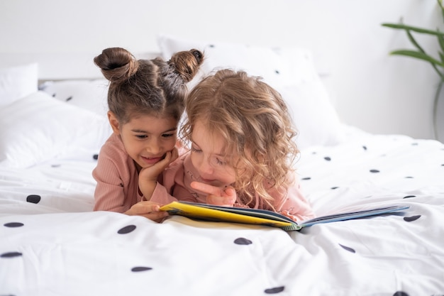 Two diverse kids girl sisters friends in pajamas reading book lying on white bedding on bed at home.
