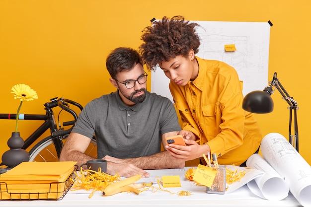 Два разных члена рабочей группы обдумывают творческие идеи для будущего проекта. женщина показывает план дизайна в смартфоне на веб-странице, позирует на рабочем столе.