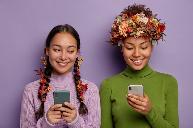 그들의 머리에 장식 단풍과 함께 휴대 전화를 사용하는 두 가지 다양한 여자
