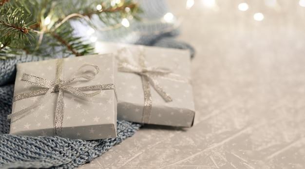 Две подарочные коробки своими руками на сером вязаном пледе с еловыми ветками и рождественскими огнями.
