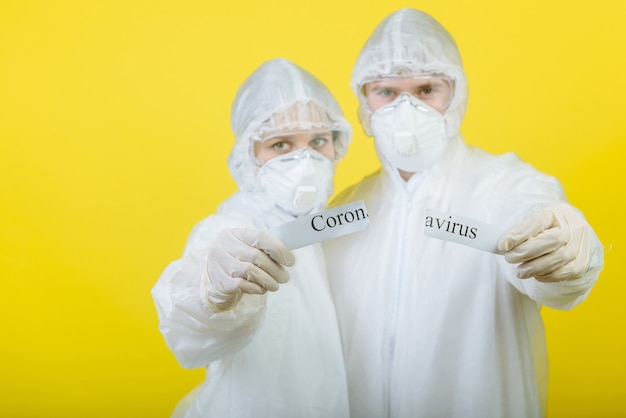 개인 보호 복 (ppe)을 입은 두 명의 의사가 코로나 바이러스라는 텍스트가있는 경고 표지판을 찢어 버렸습니다. 노란색 배경