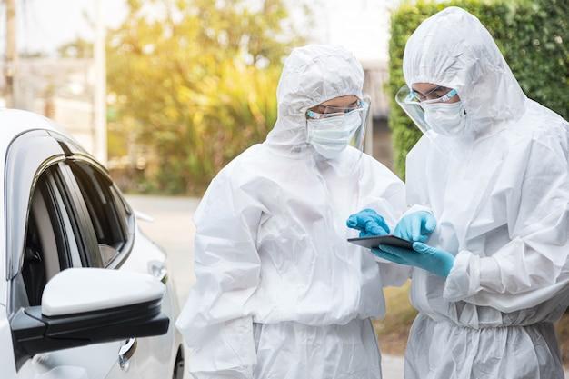 Два врача в защитном костюме сиз используют планшет для проверки информации о вспышке covid-19. концепция вируса короны и здравоохранения.