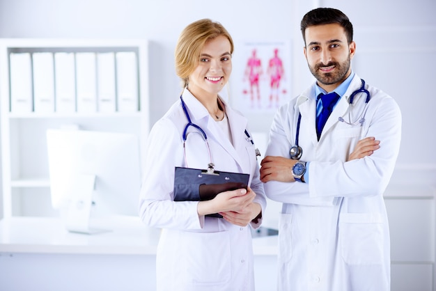 Two doctors all standing together in a consultancy room and holding patient notes