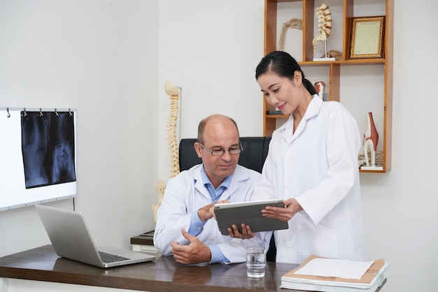 Two doctors analyzing digital x-ray on tablet pc