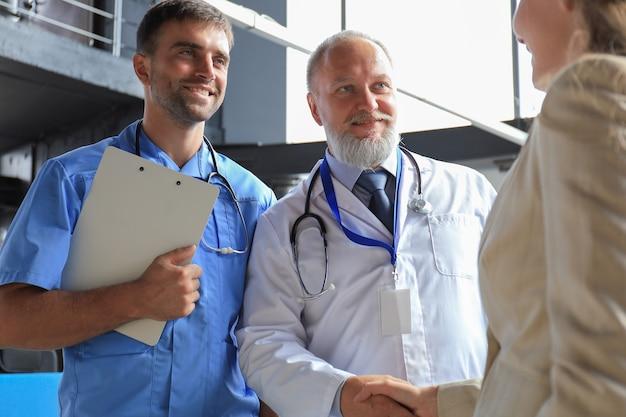 현대 의료 센터 사무실에서 상담하기 전에 두 명의 의사와 여성 환자가 악수를 하고 있습니다.