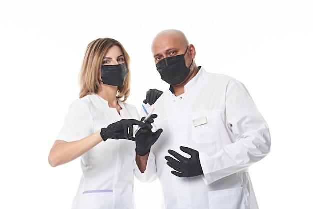 두 의사가 주사기를 손에 들고 나란히 서서 카메라를보고 있습니다. 복사 공간 흰색 절연