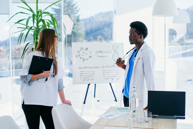 Two doctors communicate at the conference room in the hospital. african male and caucasian female medical students at meeting room at modern clinic.