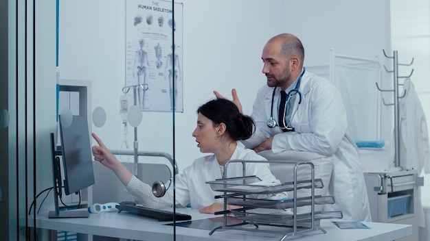Два врача консультируются по поводу медицинской проблемы через стеклянную стену, в то время как пациенты и медицинский персонал идут по коридору. система здравоохранения, частная современная медицинская клиника