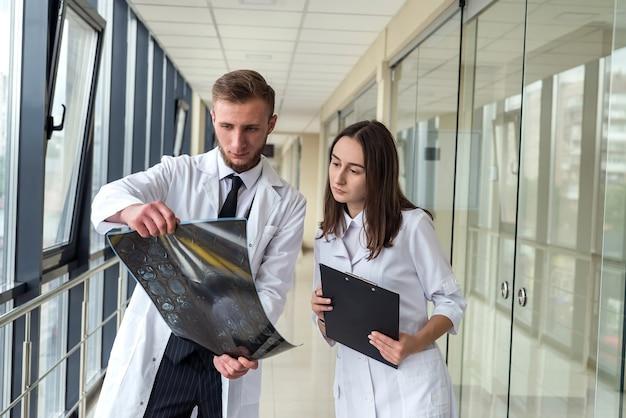 2人の医師が、入院中の患者の脳のx線mri画像の結果について話し合います。チームワーク