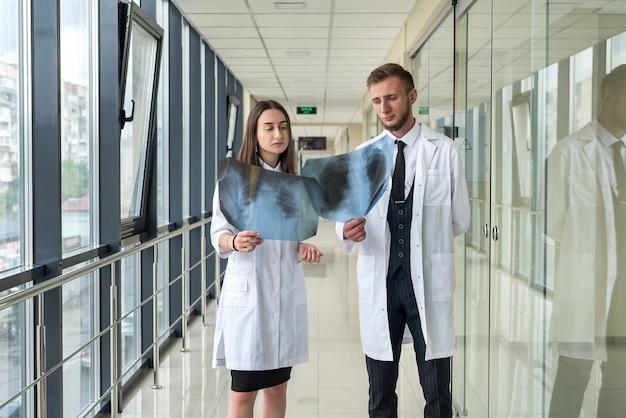 クリニックで新しいウイルスcovid19の診断のために患者の肺x線画像を調べる2人の医師