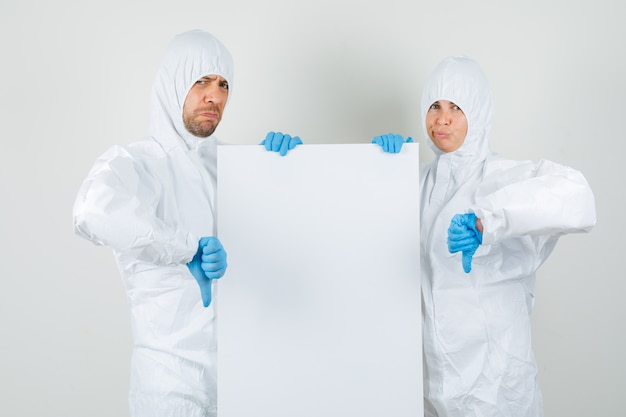 Two doctors holding blank canvas and showing thumbs down in protective suits