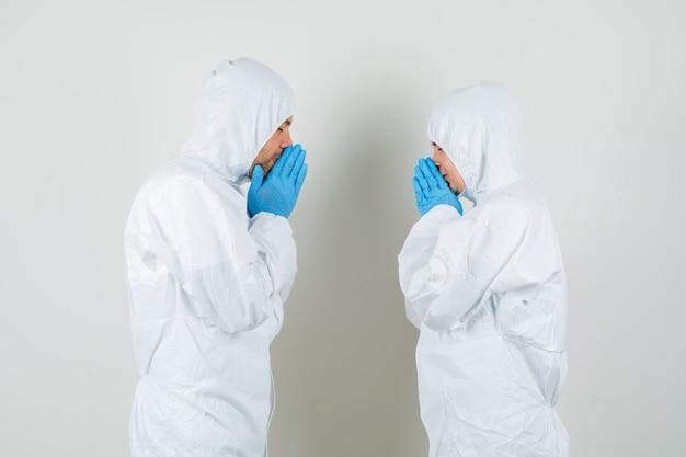 Due medici che tengono le mani nel gesto di preghiera in tute protettive
