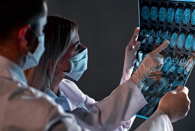 보호 마스크를 쓴 두 명의 의사가 블랙에 고립 된 환자 뇌의 x- 레이 또는 mri 스캔을보고 논의합니다.
