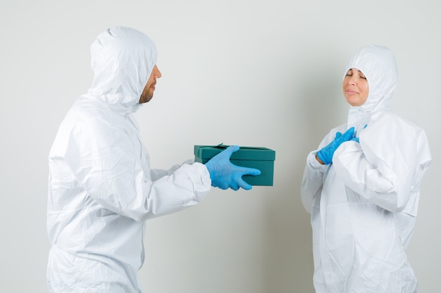 Два доктора в защитном костюме, перчатках передают друг другу подарочную коробку и выглядят прекрасно.