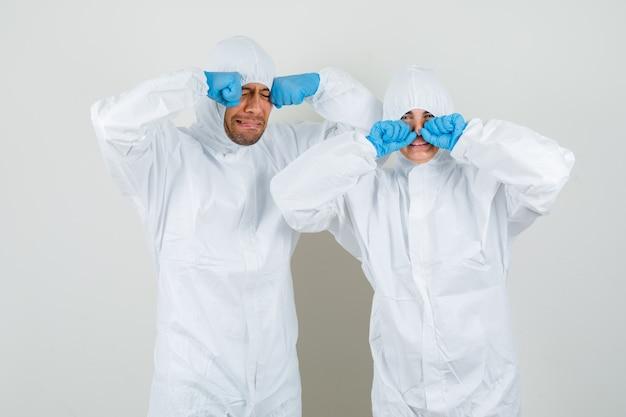 防護服を着た2人の医師、子供のように泣きながら怖がっている手袋が目をこすります