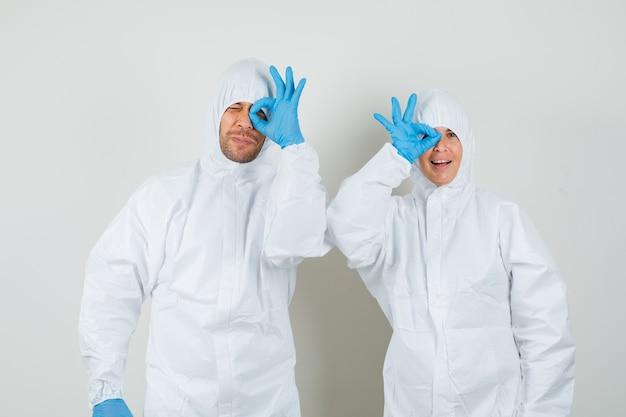 Два врача в защитных костюмах, перчатки показывают знак ок на глаз
