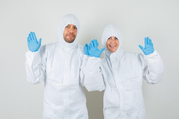 보호 복에 두 의사, 손바닥을 보여주는 장갑과 쾌활한 찾고
