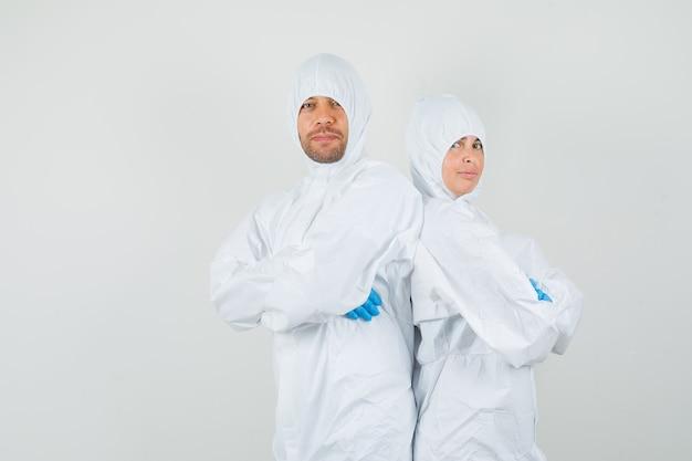 Два врача в защитных костюмах, перчатках со скрещенными руками выглядят уверенно