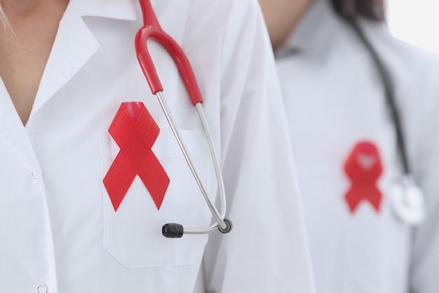 Два врача в белом халате с красной лентой на груди